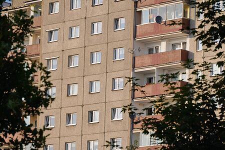 gray multi-storey panel house in a residential area of the big city among the trees, Windows and loggias, gray wall, the outside of the house, trees near the houses in city Фото со стока