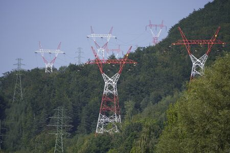 High-voltage power line. red and white power poles in a hilly green forest. transmission of electricity from station to consumers.