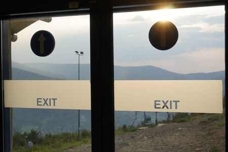 doors with stickers with exit information on the background of mountains and forests, misty sky and sunlight. exit in clouds and mountains. Banco de Imagens