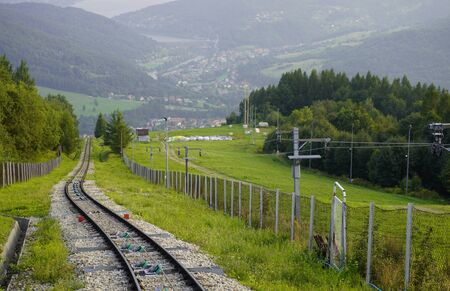 railway for the trailer in the mountains at fence, the mountains in the summer in the grass and forests, at the foot of the house and the lake. transport links for transportation of people