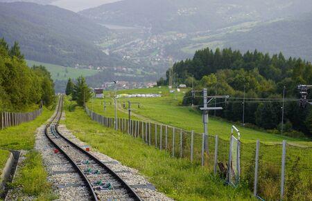 spoor voor de trailer in de bergen bij hek, de bergen in de zomer in het gras en de bossen, aan de voet van het huis en het meer. vervoersverbindingen voor het vervoer van mensen