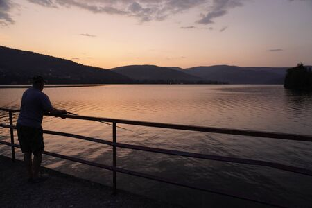 fisherman stands on pier by the lake, mountainous terrain against the sunset. bright sunset in the mountains. outdoor activity.