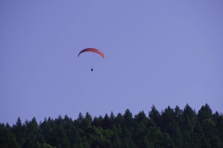 a man flies paraglider from the mountain, surrounded by forests. flying under wing. outdoor activity