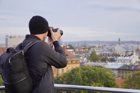 silhouette of man with a camera on the background of the city. tourist, autumn photo tours of the cities. photo from the roof in Krakow. top view