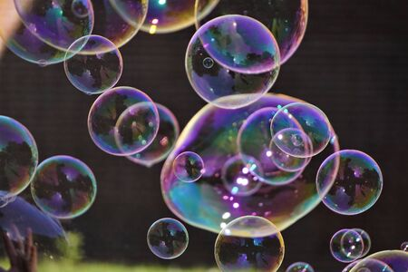 large iridescent soap bubbles of different sizes on the streets of city. screensaver, copy space, background.