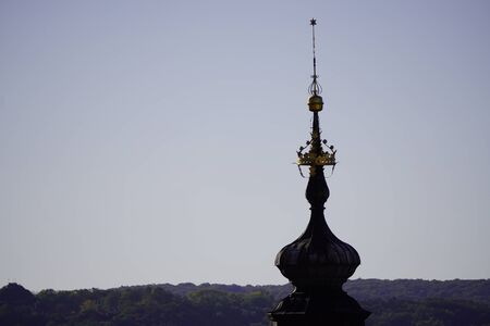 silhouette of the spire of the old Church on the background of light sky and forest. gold crown on the spire of the Church. forest and mound in distance