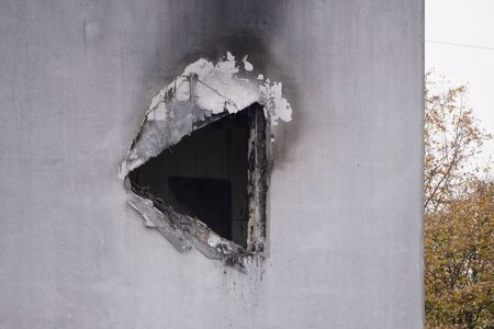 hole in concrete wall after the fire, smoke soot on the light paint, the need for repair after the fire, restoration
