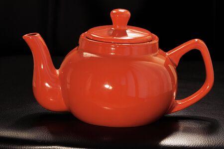 leuchtend rote Teekanne aus Keramik oder Teekanne auf schwarzem Hintergrund. Kleiner Wasserkocher, Nachmittagstee - heißen Tee trinken.