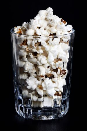 many crunchy popcorns are in a clear glass on a dark black background, food or sneak for the movies and the circus. A dark high angle photo. Traditional food is prepared and ready to eat, vertical orientation.