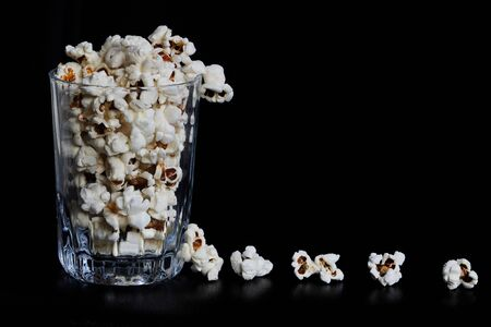 many crunchy popcorns are in a clear glass on a dark black background, food or sneak for the movies and the circus. A dark high angle photo. popcorn is spreading in line, the seeds are near the glass. Stock fotó