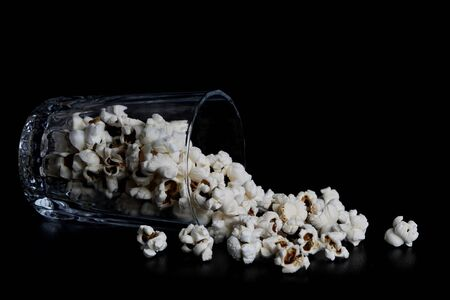 popcorn spilled from a glass on a black background. Scattered, on his back in a glass. photo in low key