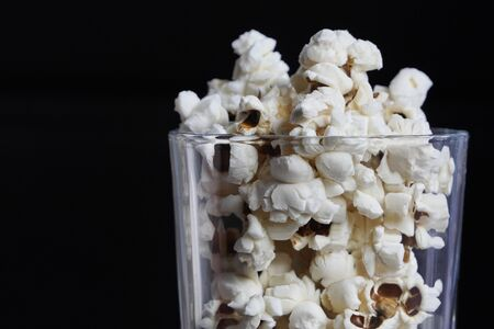 many crunchy popcorns are in a clear glass on a dark black background, food or sneak for the movies and the circus. A dark high angle photo. Traditional food is prepared and ready to eat, horizontal orientation.
