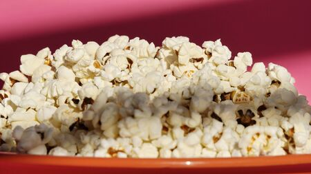 coral plate with popcorn on the table on a pink background. a snack, a treat to the cinema or the circus. exploding corn kernels.