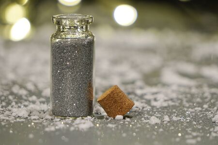 jar with gray glitter on snowy background.powder for shiny,girls things.flatley, Christmas background with lights