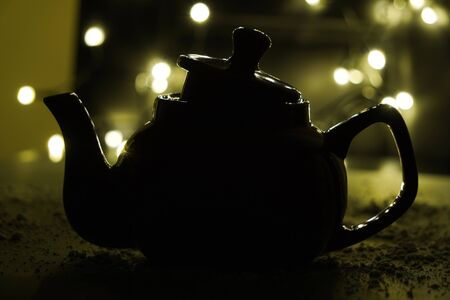 the shadow of the kettle on dark background and light bulbs. Dark background. Vintage black ceramic teapot.