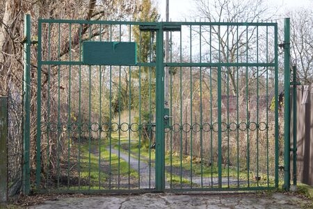 green iron fence with gate at the forest or field entrance is forbidden, secret, personal or military territory. protection of possessions from outsiders.