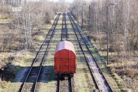 one red boxcar or carriage stands on the rails among the trees on Sunny autumn or spring day. The trees are leafless, but the grass is still green. abandoned freight station. no people, copy space