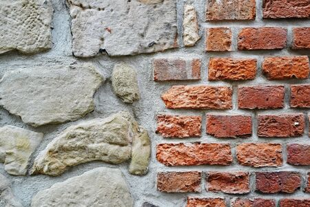 Fragment of restoration of masonry of red old brick and big stones contrast. different size and color bricks, background, screensaver place for text, copyspace.