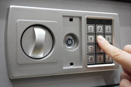 the man dials the code to close the safe. Grey safe closure, numeric keypad. A man presses the keys on the digital panel on the safe Banque d'images