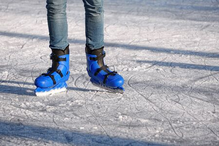 Bright Blue plastic skates in background of scratched ice in a Sunny day. entertainment in the winter season, active sports. legs of a man in blue skates rides on an ice rink.