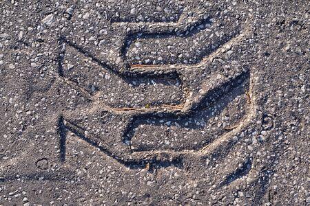 footprints on asphalt from cars or wheels. soft asphalt after the heat flow, copyspace Stock Photo