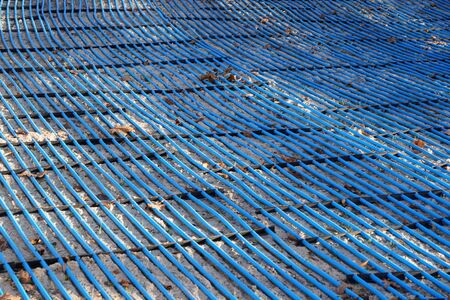 plastic blue ice freezing tubes evenly stacked in rows and secured, artificial ice for skating on holidays. watering system of plants in garden. Warm floor or road contraction