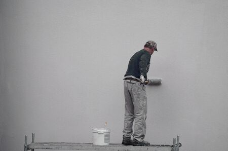 male painter paints the wall with a roller blue paint. outdoor work in an apartment building and multi-storey building.
