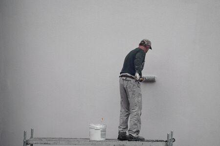 pintor pinta la pared con un rodillo de pintura azul. trabajo al aire libre en un edificio de apartamentos y edificio de varios pisos.