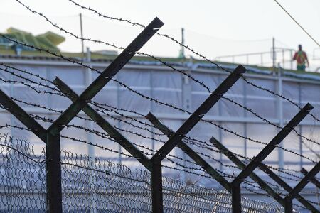 fence made of mesh and barbed wire near the construction of an industrial building. restriction of access to the territory of an industrial facility.