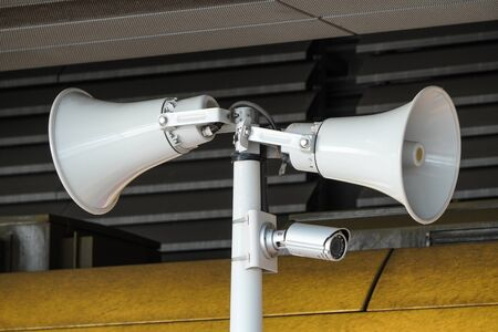 two white loudspeakers and a security camera on pole in a public place. providing security in the city, notification of emergencies, informing passengers, technical means of notification and control.