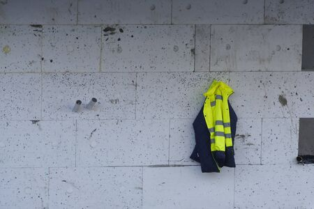 workers' bright clothes hang on a hook on the front of the building. warm jacket for changing clothes during work in the cold season-winter or autumn or spring. Banque d'images