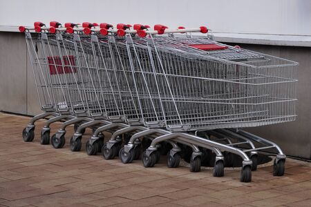 the iron carts for products in supermarkets or stores. Store parking trolleys with red handles. transportation of heavy products during purchases. Grocery shopping carts piled into each other