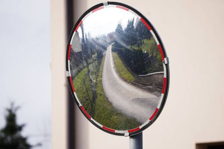 dirty mirror stands at a bend in the road in a mountain village to help visibility in traffic or prevent accidents. in the reflection of the road, house and fences.