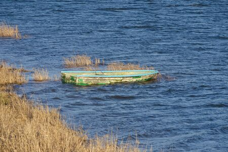an old lonely abandoned fishing boat stands on shore on water on Sunny and windy day, light waves, there is no motor. painted with green peeling paint. yellowed grass grows on shore Zdjęcie Seryjne