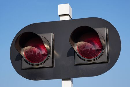 traffic light for a railway crossing, two red lights against a blue sky. forbidding sign for leaving the tracks. traffic safety, train warning for cars and pedestrians