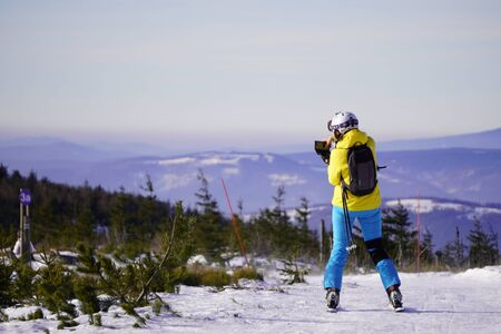 woman in bright blue and yellow ski clothes photographs a view of the mountains on a Sunny, clear day at the peak of the mountain. active winter recreation, skiing and snowboarding in the mountains. Stock fotó