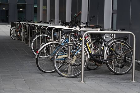 Bicycle Parking under roof of a gray office building. use of eco-friendly and sports transport in the city to move. Bicycles are strapped in a row. Reklamní fotografie