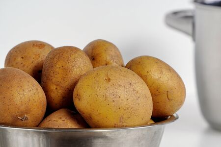 Untreated unpeeled organic fresh raw potatoes in their skins in metal plate or pan on a white background. vegetable dishes, healthy food.
