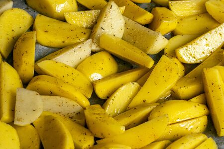 Heap fresh yellow raw peeled potatoes sliced into pieces with oil and spices for baking on baking sheet. Chopped Potatoes ready for French fries. Healthy vegan or vegetarian autumn ingredient. Reklamní fotografie