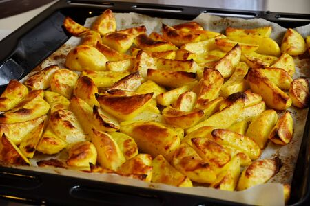 Pile of fresh delicious yellow baked or stewed potatoes with herbs with crust. Homemade French fries. Healthy vegan or vegetarian autumn ingredients.