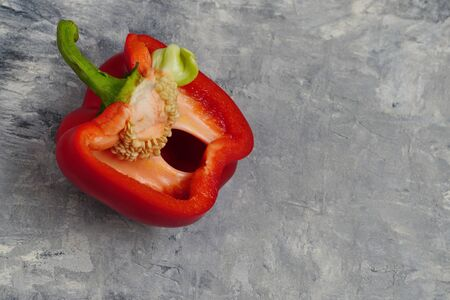 half a red pepper with seeds and green tail on a gray concrete background.