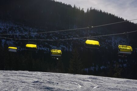 Ropeway empty chairlift in the mountains with a yellow cover cabin or capped. Chairlift going up mountain. Szczyrk, Silesian.