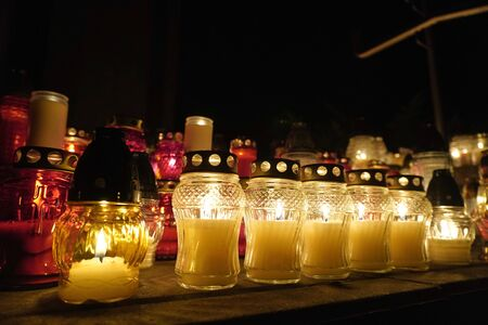 burning colorful candles in jars in cemetery on the occasion souls of the deceased at night Poland Religion tradition. holiday as the remembrance day. graveyard on the day of the dead