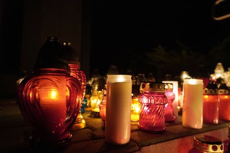 burning colorful candles in jars in cemetery on the occasion souls of the deceased at night Poland Religion tradition. holiday as the remembrance day. graveyard on the day of the dead Foto de archivo