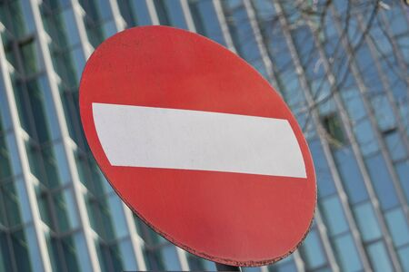 road sign prohibiting travel in this direction on the background of concrete and glass building. the rules of the road in the modern city.
