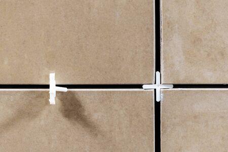 Laying ceramic tiles using plastic crosses. Use plastic crosses to align seams. Renovation or repair concept Standard-Bild