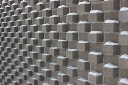 Grey brick texture, the bricks protruding with covered Paving Snow.