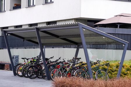 Parking moderne avec un toit pour vélos près d'un immeuble avec un grand nombre de vélos. Transports écologiques et sportifs en ville.