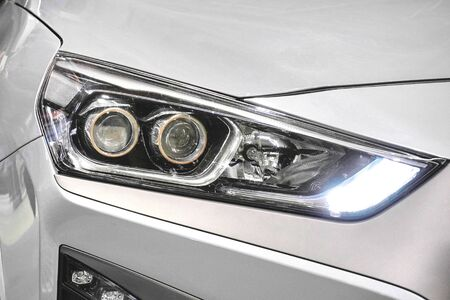 Led headlight of a white modern car. Modern trends in the automotive industry. Head optics of the machine