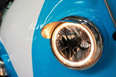 Headlight of a white and blue retro car. Modern trends in the automotive industry. Head optics of the machine